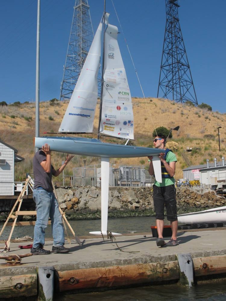 Jamie and Tobias carrying the boat back for repairs on the halyard